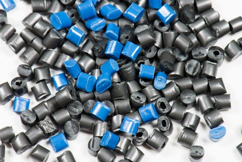 blue and black plastic granulate for injection moulding on white background